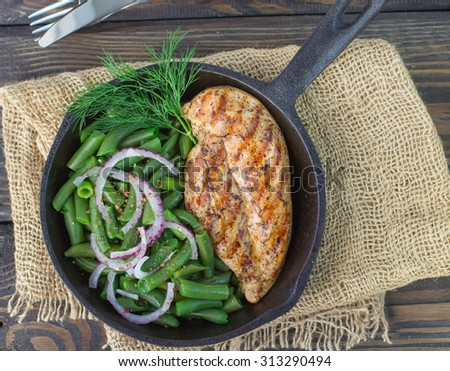 Grilled chicken breast and green beans in a cast iron skillet on the table. Selective focus - stock photo