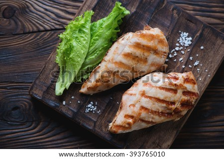 Grilled chicken breast filet, rustic wooden setting, top view