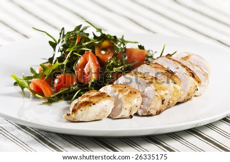 Grilled chicken breast served with salad - stock photo