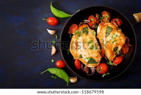 Grilled Chicken breast stuffed with tomatoes, garlic and basil in pan. Top view