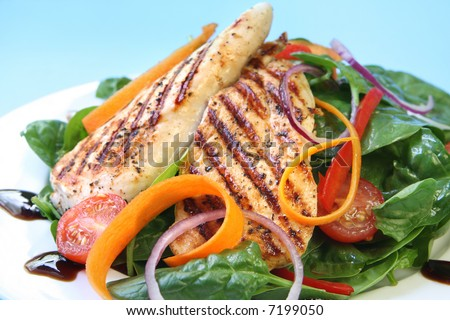 Grilled chicken breast with a spinach salad, with a balsamic reduction. - stock photo