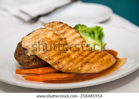 Grilled chicken breast with baked potato, carrots and broccoli