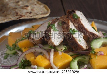 Grilled chicken breast with fresh mango salad and naan bread - stock photo