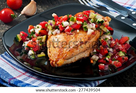 Grilled chicken breast with fresh tomato salsa on black plate - stock photo