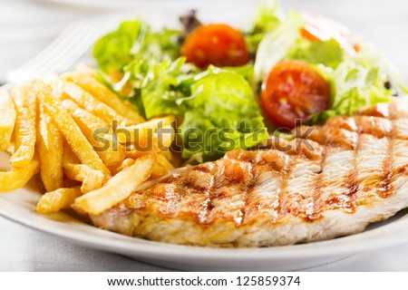 Grilled chicken breast with fries and salad - stock photo