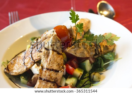 Grilled chicken breast with Greek salad - stock photo