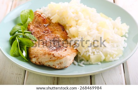 Grilled chicken breast with pineapple rice on plate - stock photo