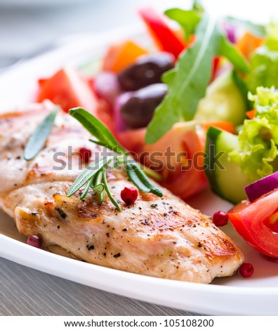 Grilled chicken breast with tomatoes, red pepper, organic kalamata and green olives, red onion, lettuce and fresh rocket and rosemary. Home made food. Concept for a tasty and healthy meal. Close up