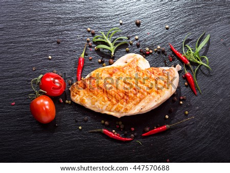 grilled chicken breast with vegetables on dark background - stock photo
