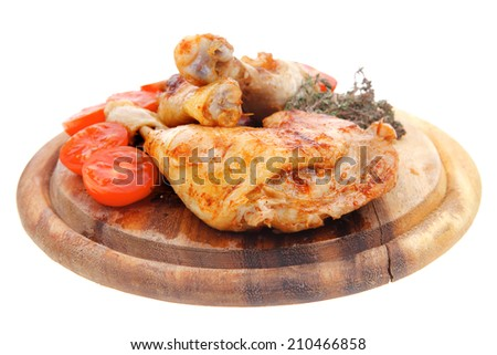 grilled chicken drumstick with tomatoes and thyme on wooden plate isolated over white background - stock photo