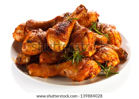 Grilled chicken drumsticks and vegetables on white background