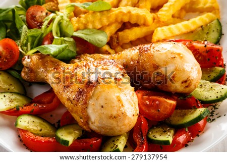 Grilled chicken drumsticks with chips and vegetables  - stock photo