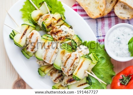 Grilled chicken filet kebab, shashlik on skewers with rolled zucchini, tasty picnic dish