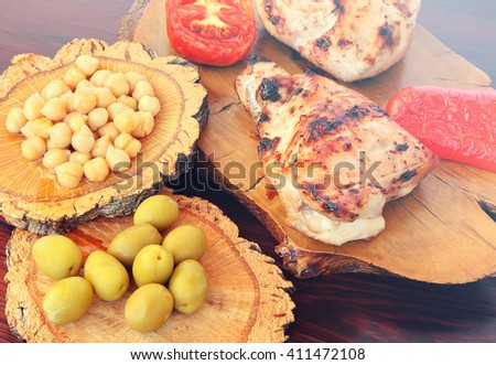 Grilled chicken fillet and tomatoes with fresh fruit (red fresh grapes) served with olives and  hummus on the wood. Mediterranean cuisine. Toned colors vintage photo  - stock photo