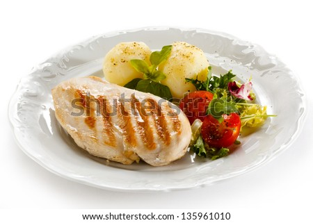 Grilled chicken fillet, French fries and vegetables - stock photo