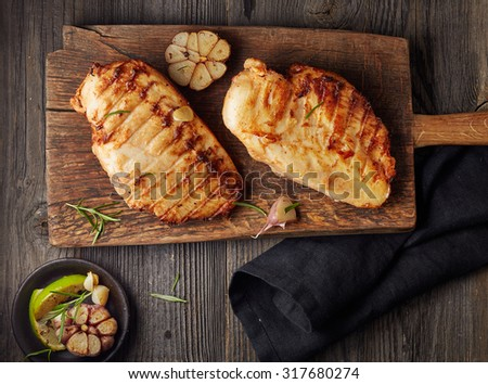 Grilled chicken fillet on wooden cutting board - stock photo