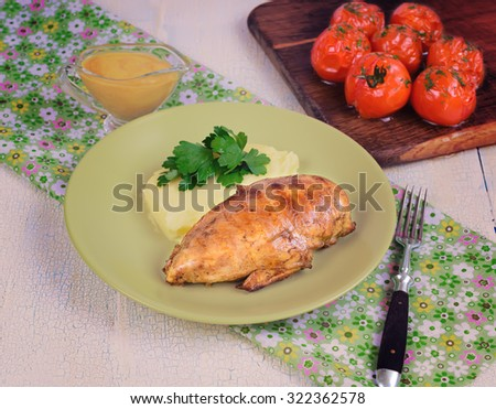 Grilled chicken fillet with mashed potatoes and grilled tomatoes. Rustic style. - stock photo