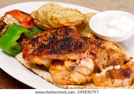 Grilled chicken fillets, with potatoes and vegetables and mayo garlic dip