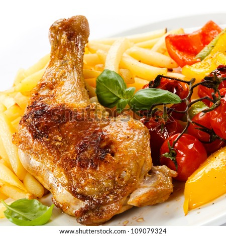 Grilled chicken leg, French fries and vegetables - stock photo