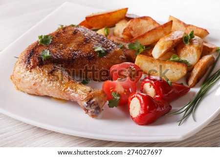 Grilled chicken leg, roasted potatoes and vegetables on a plate close-up. horizontal