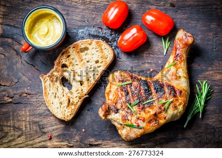 Grilled chicken leg with toast and cherry tomato - stock photo