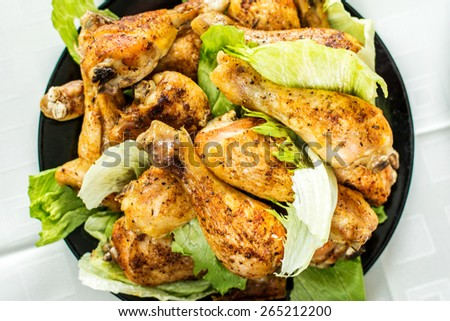 Grilled chicken legs and salad on black plate - stock photo
