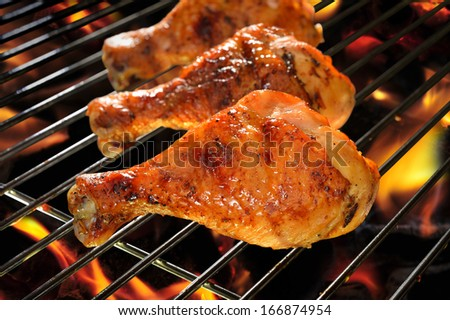 Grilled chicken Legs on the flaming grill.