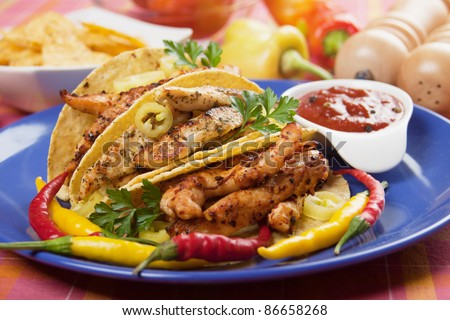 Grilled chicken meat, vegetable and hot chili peppers in taco shells ...