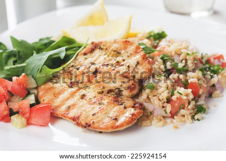 Grilled chicken meat with bulgur wheat and rocket salad - stock photo