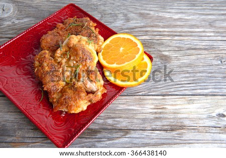 Grilled chicken on a red plate on a wooden background - stock photo