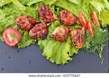 Grilled chicken  on green  salad leaves with tomato, dills on dark stone board
