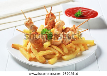 Grilled chicken on sticks and French fries