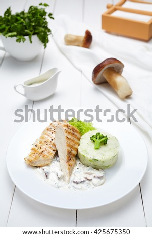 Grilled chicken or turkey breast fillet with broccoli, mashed potatoes and mushrooms in cream sauce. Dietetic restaurant menu meal. - stock photo