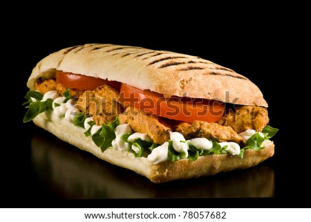 Grilled chicken sandwich on a black background - stock photo