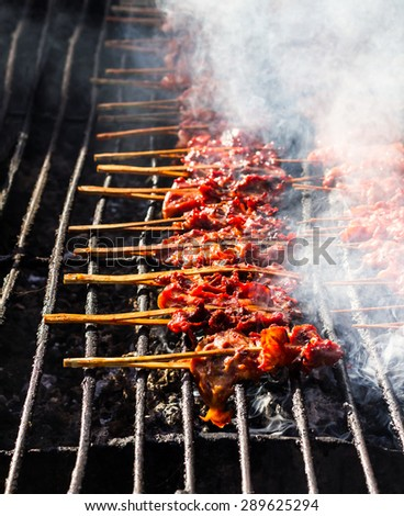 Grilled chicken skewers on a row of steel bars placed on hot coals with much smoke. - stock photo