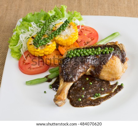 Grilled Chicken steak with black pepper sauce, In white dish on brown cloth / Select focus