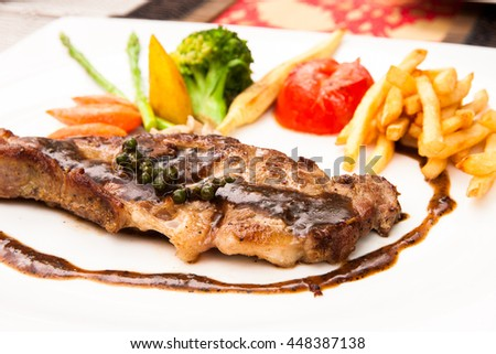 Grilled chicken steak with Thai style sauce pepper side dish on white plate.