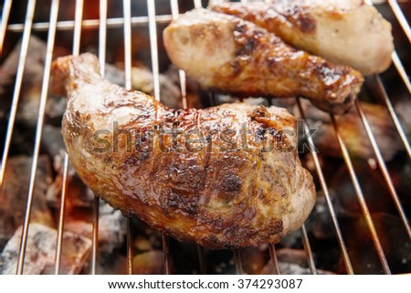 Grilled chicken thigh over flames on a barbecue.