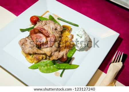 Grilled chicken thighs with crunchy vegetables served with grilled potato, bacon and chive dip - stock photo