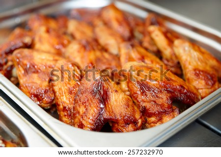 Grilled chicken wings in stainless steel container, commercial kitchen