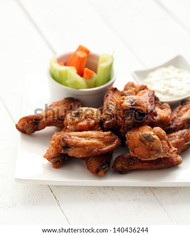 Grilled chicken wings with sauce and vegetables - stock photo