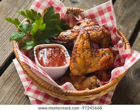 grilled chicken wings with tomato sauce in basket, selective focus - stock photo