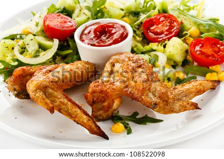 Grilled chicken wings with vegetable salad - stock photo