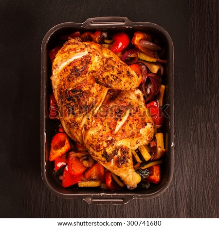 Grilled chicken with baked vegetables and spicy sauce on black stone background. Selective focus. Top view - stock photo