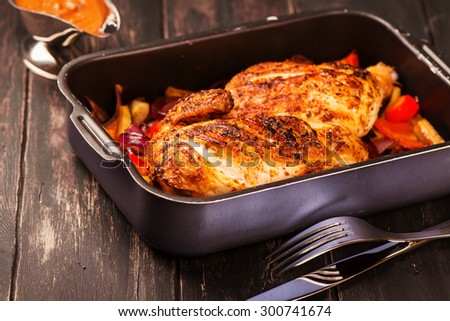 Grilled chicken with baked vegetables and spicy sauce on black wooden background. Selective focus