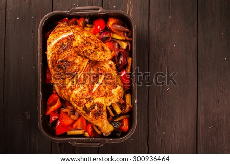 Grilled chicken with baked vegetables and spicy sauce on black wooden background. Selective focus. Top view - stock photo