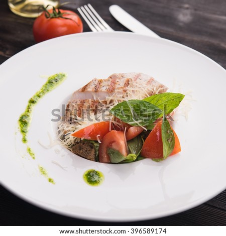 grilled chicken with basil and tomato in restaurant table