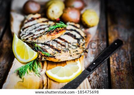 Grilled chicken with potatoes and herbs on wooden background - stock photo