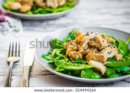 Grilled chicken with spinach,arugula and peas on rustic wooden background - stock photo