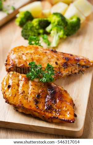 grilled ckicken breast with broccoli,potato and parsley on wooden board